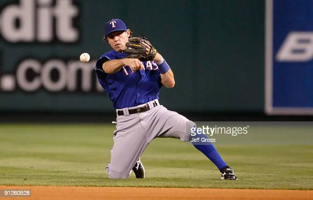 Ian Kinsler of the Texas Rangers throws from his knees to get Robb Quinlan of the Los Angeles Angels of Anaheim in the seventh inning at Angel...