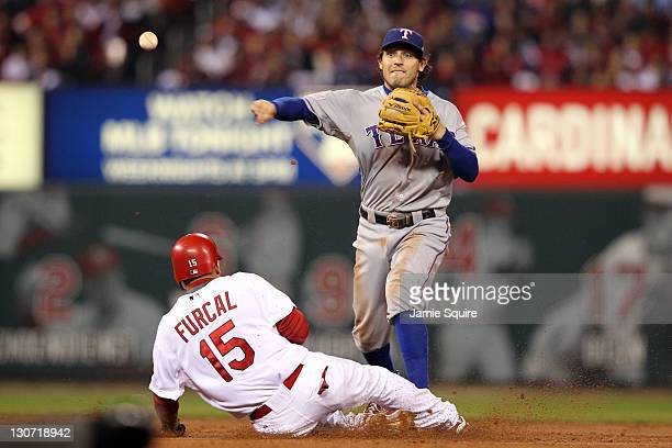 Ian Kinsler of the Texas Rangers turns the double play as Rafael Furcal of the St Louis Cardinals slides into second base in the second inning during...