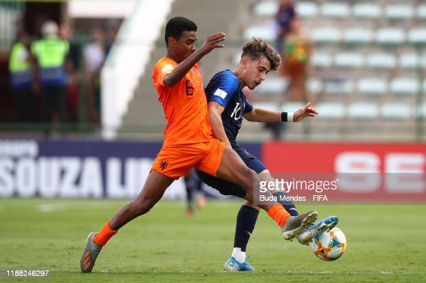 Ian Maatsen of Netherlands looks to break past Adil Aouchiche of France during the 3rd Place Playoff match between the Netherlands and France at the...