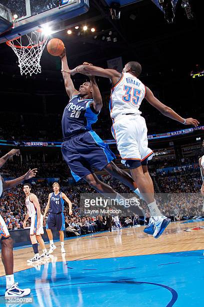 Ian Mahinmi of the Dallas Mavericks shoots while trying to keep Kevin Durant of the Oklahoma City Thunder from interfering during an NBA game on...