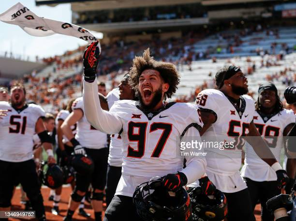 Ian Marshall of the Oklahoma State Cowboys celebrates with teammates after defeating the Texas Longhorns at Darrell K Royal-Texas Memorial Stadium on...