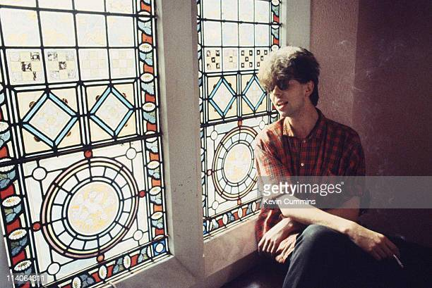 Ian McCulloch of british postpunk group Echo And The Bunnymen slooks out a window while smoking a cigarette circa 1984