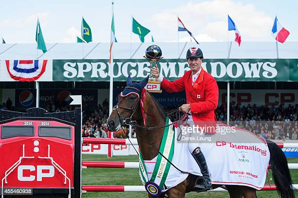 Ian Millar of Canada riding Dixson raises the CP International trophy after winning the individual jumping equestrian on the final day of the Masters...