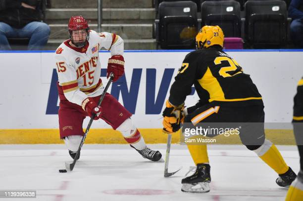 Ian Mitchell of the Denver Pioneers skates with the puck against Janis Jaks of the American International Yellow Jackets during the NCAA Division I...