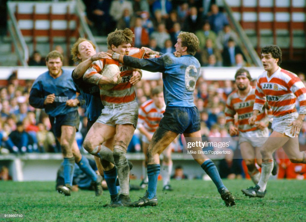 Ian Potter of Wigan (with the ball) is tackled by Steve Peters (6) and Peter Gorley of St Helens during their rugby league match on 5th April 1985.
