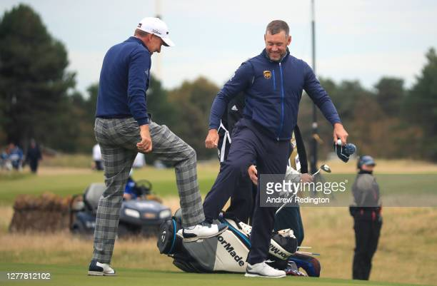 Ian Poulter and Lee Westwood of England do a foot tap as a socially distanced acknowledgement after their first round of the Aberdeen Standard...