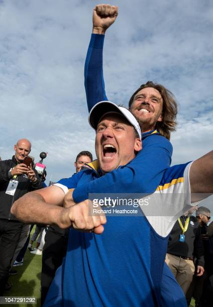 Ian Poulter and Tommy Fleetwood celebrate victory after the singles matches of the 2018 Ryder Cup at Le Golf National on September 30, 2018 in Paris,...