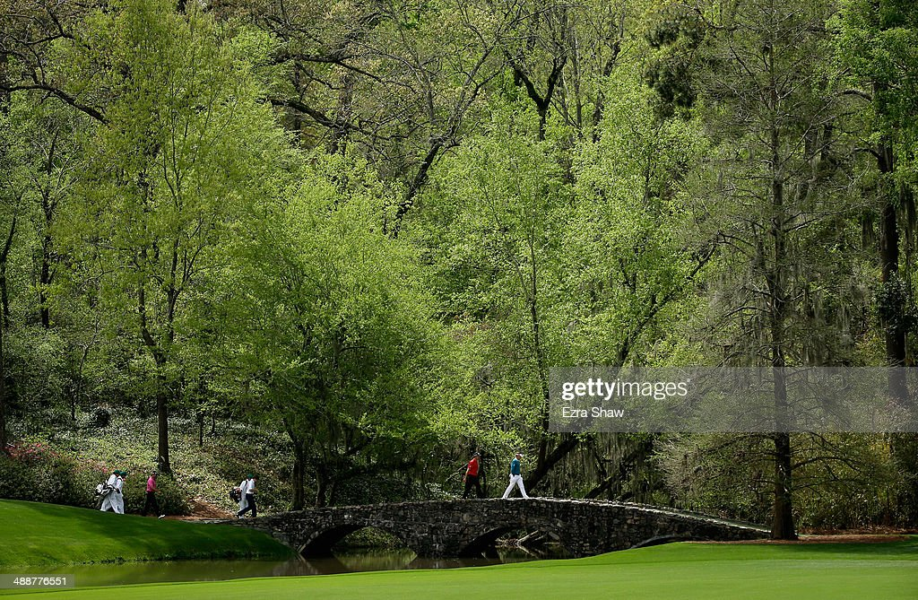 Ian Poulter of England and Henrik Stenson of Sweden walk across the Nelson Bridge on the 13th hole at Augusta National Golf Club on April 8, 2014 in Augusta, Georgia.