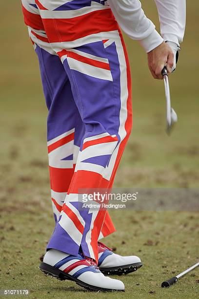 Ian Poulter of England hits balls on the practice ground wearing union jack trousers prior to beginning his game during the first round of the 133rd...