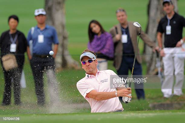 Ian Poulter of England hits his ball out of a bunker and onto the green during the third day of the Hong Kong Open golf tournament at the Hong Kong...