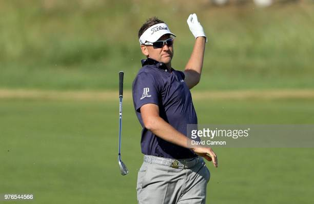 Ian Poulter of England lets go of his club after playing his second shot on the 13th hole during the third round of the 2018 US Open at Shinnecock...