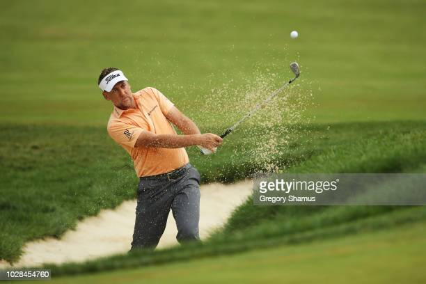 Ian Poulter of England plays a shot from a bunker on the 12th hole during the second round of the BMW Championship at Aronimink Golf Club on...