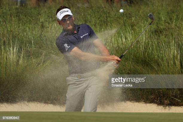 Ian Poulter of England plays a shot from a bunker on the third hole during the third round of the 2018 US Open at Shinnecock Hills Golf Club on June...