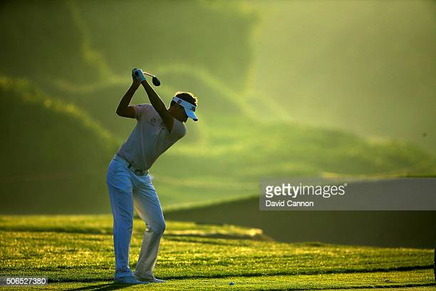 Ian Poulter of England plays his second shot at the par 4 14th hole during the completion of the fog delayed third round of the 2016 Abu Dhabi HSBC...