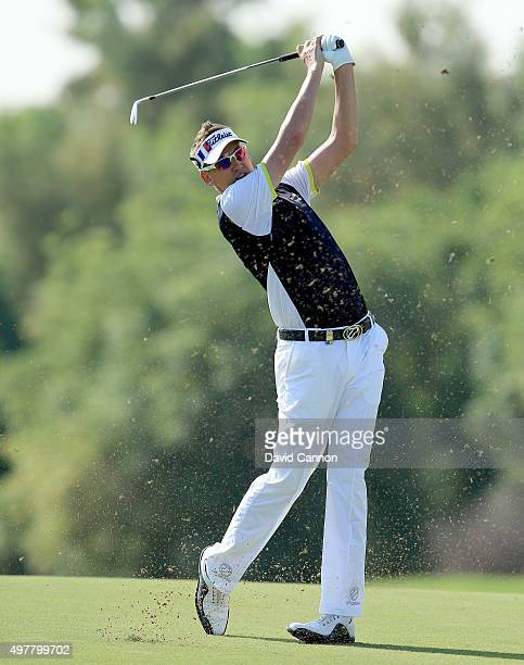 Ian Poulter of England plays his second shot at the par 4, third hole wearing a visor coloured with the French flag in remembrance of the Paris...