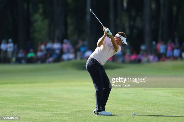 Ian Poulter of England plays his second shot on the 15th hole during the final round of THE PLAYERS Championship at the Stadium course at TPC...