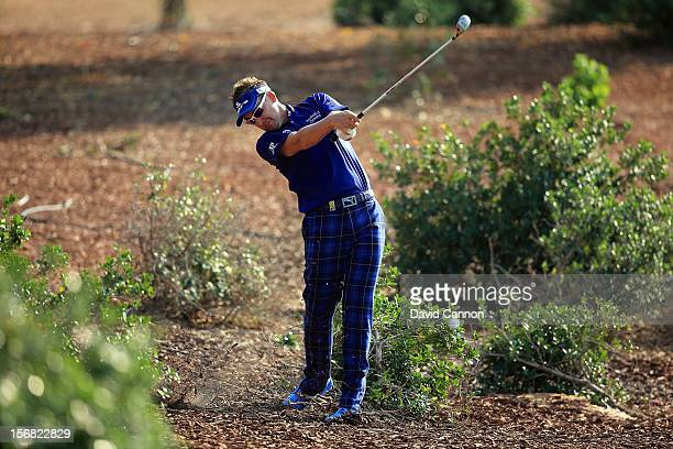 Ian Poulter of England plays his second shot on the par four 12th hole during the first round of the 2012 DP World Tour Championship on the Earth...