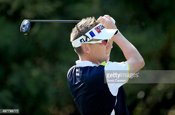 Ian Poulter of England plays his tee shot at the par 3 fourth hole wearing a visor coloured with the French flag in remembrance of the Paris...