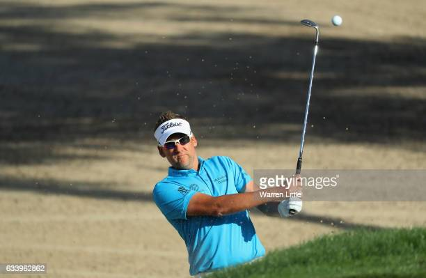 Ian Poulter of England plays out of the 15th greenside bunker during the final round of the Omega Dubai Desert Classic on the Majlis course at...