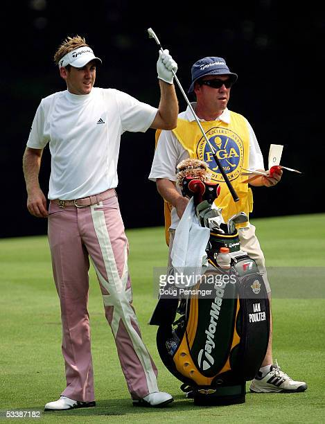 Ian Poulter of England pulls a club as his caddie Michael Donaghy checks the yardage on the second hole during the final round of the 2005 PGA...