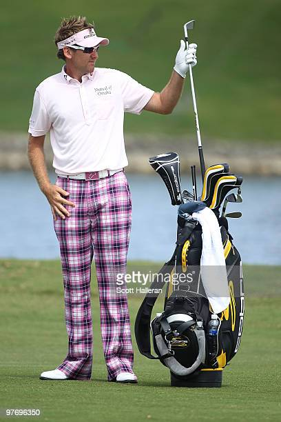 Ian Poulter of England pulls a club from his bag on the 18th hole during the final round of the 2010 WGCCA Championship at the TPC Blue Monster at...