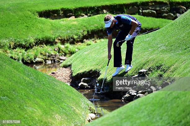 Ian Poulter of England retrieves his ball out of Rae's Creek during a practice round prior to the start of the 2016 Masters Tournament at Augusta...