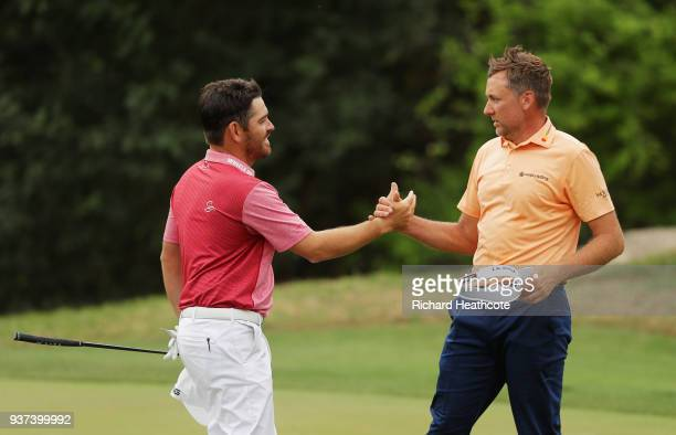 Ian Poulter of England shakes hands with Louis Oosthuizen of South Africa after defeating him 21 on the 17th green during the fourth round of the...