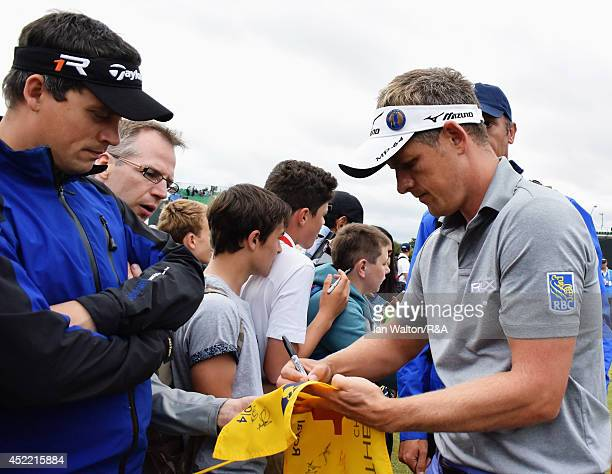 Ian Poulter of England signs his autograph for a fan during a practice round prior to the start of the 143rd Open Championship at Royal Liverpool on...