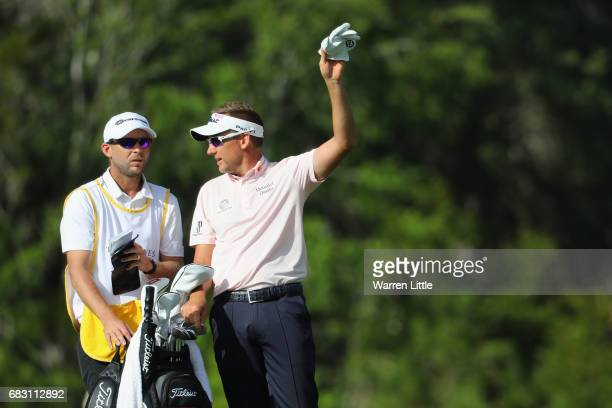 Ian Poulter of England talks with his caddie James Walton during the final round of THE PLAYERS Championship at the Stadium course at TPC Sawgrass on...