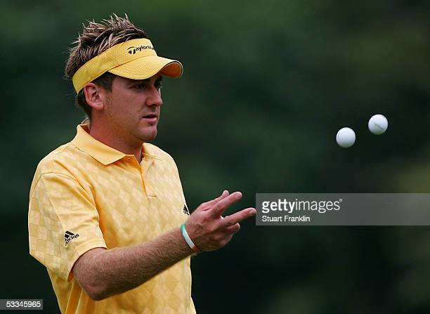 Ian Poulter of England tosses a couple of balls to his caddie during the second practice round of the 2005 PGA Championship at Baltusrol Golf Club on...