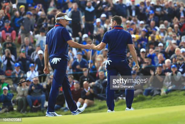 Ian Poulter of Europe and Rory McIlroy of Europe celebrate during the afternoon foursome matches of the 2018 Ryder Cup at Le Golf National on...