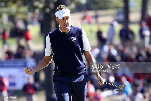 Ian Poulter of Europe celebrates after holing a birdie putt on the 12th hole during the Singles Matches for The 39th Ryder Cup at Medinah Country...