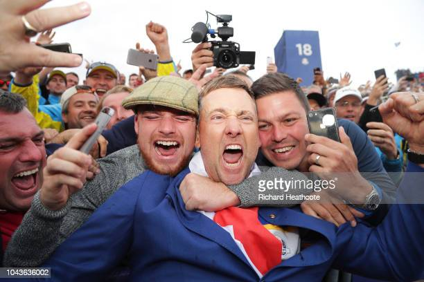 Ian Poulter of Europe celebrates after winning The Ryder Cup with supporters during singles matches of the 2018 Ryder Cup at Le Golf National on...