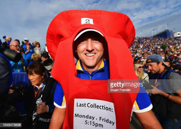 Ian Poulter of Europe celebrates winning The Ryder Cup after taking a Post Box outfitt off of a fan during singles matches of the 2018 Ryder Cup at...