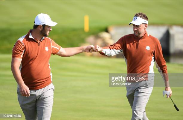 Ian Poulter of Europe celebrates with Jon Rahm of Europe during the morning fourball matches of the 2018 Ryder Cup at Le Golf National on September...