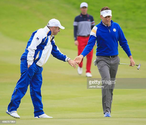 Ian Poulter of Europe is encouraged by Europe team captain Paul McGinley as he walks towards the 8th green during the Singles Matches of the 2014...