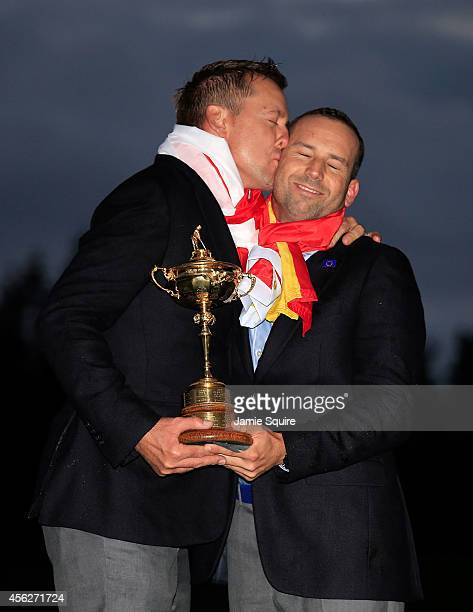 Ian Poulter of Europe kisses Sergio Garcia as they pose with the Ryder Cup trophy after the Singles Matches of the 2014 Ryder Cup on the PGA...