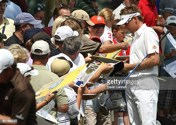 Ian Poutler of England signs his autograph for fans during a practice round prior to the 90th PGA Championship at Oakland Hills Country Club on...