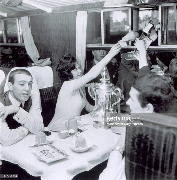 Ian St John with others sitting at a railway carriage table with a trophy on 2 May 1965. Ian St John was a Scottish footballer who started his...