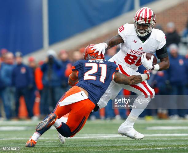 Ian Thomas of the Indiana Hoosiers runs the ball after a catch as Patrick Nelson of the Illinois Fighting Illini attempts the tackle at Memorial...