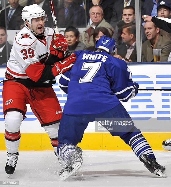 Ian White of the Toronto Maple Leafs checks Patrick Dwyer of the Carolina Hurricanes during their NHL game January 12 2010 at the Air Canada Centre...