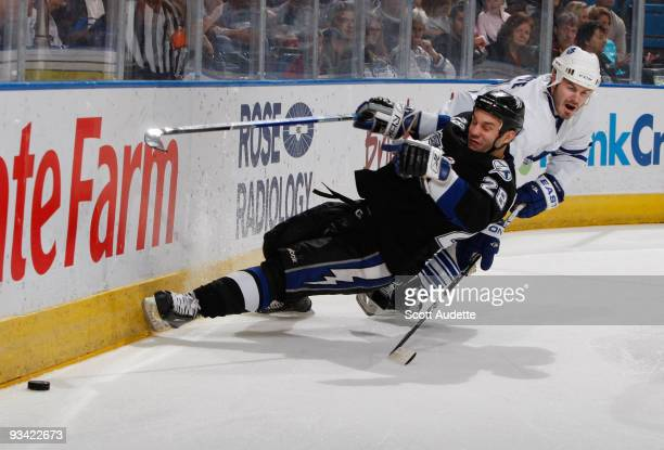Ian White of the Toronto Maple Leafs prevents Zenon Konopka of the Tampa Bay Lightning from getting to the puck along the boards during the first...