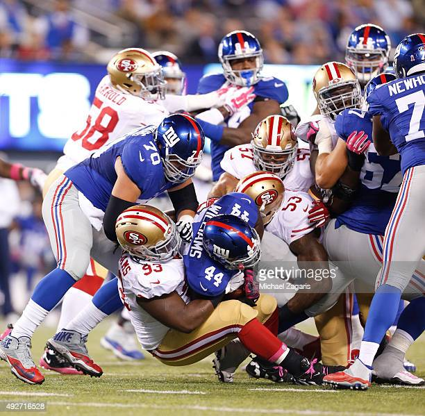 Ian Williams NaVorro Bowman and Michael Wilhoite of the San Francisco 49ers tackle Andre Williams of the New York Giants during the game at MetLife...