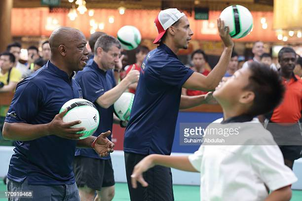 Ian Wright Dennis Irwin and Rio Ferdinand takes part in a football clinic with students from designated charities and local Singapore schools during...