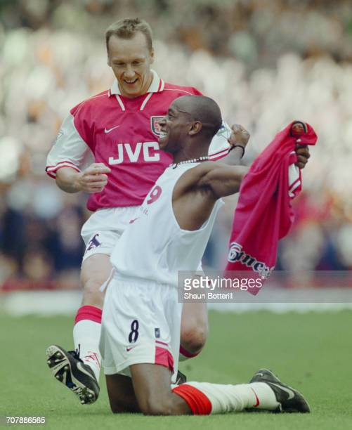 Ian Wright of Arsenal football club takes off his shirt and celebrates with team mate Lee Dixon after breaking Cliff Bastin's Arsenal goalscoring...