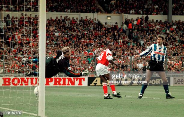 Ian Wright of Arsenal scores past Sheffield Wednesday goalkeeper Chris Woods as defender Paul Warhurst looks on during the FA Cup Final at Wembley...
