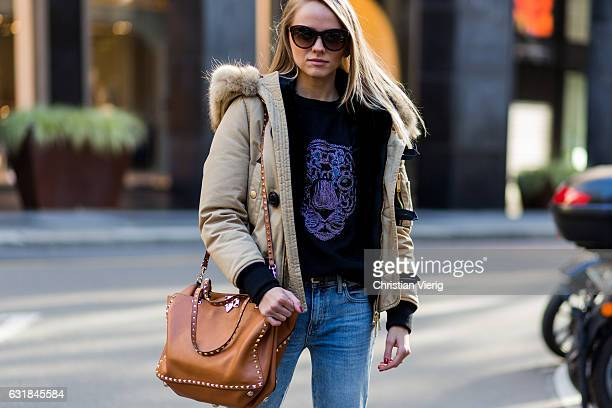 Iana Cojuhari is wearing a Kenzo sweater down feather parka ripped denim jeans brown Valentino bag at No 21 during Milan Men's Fashion Week...
