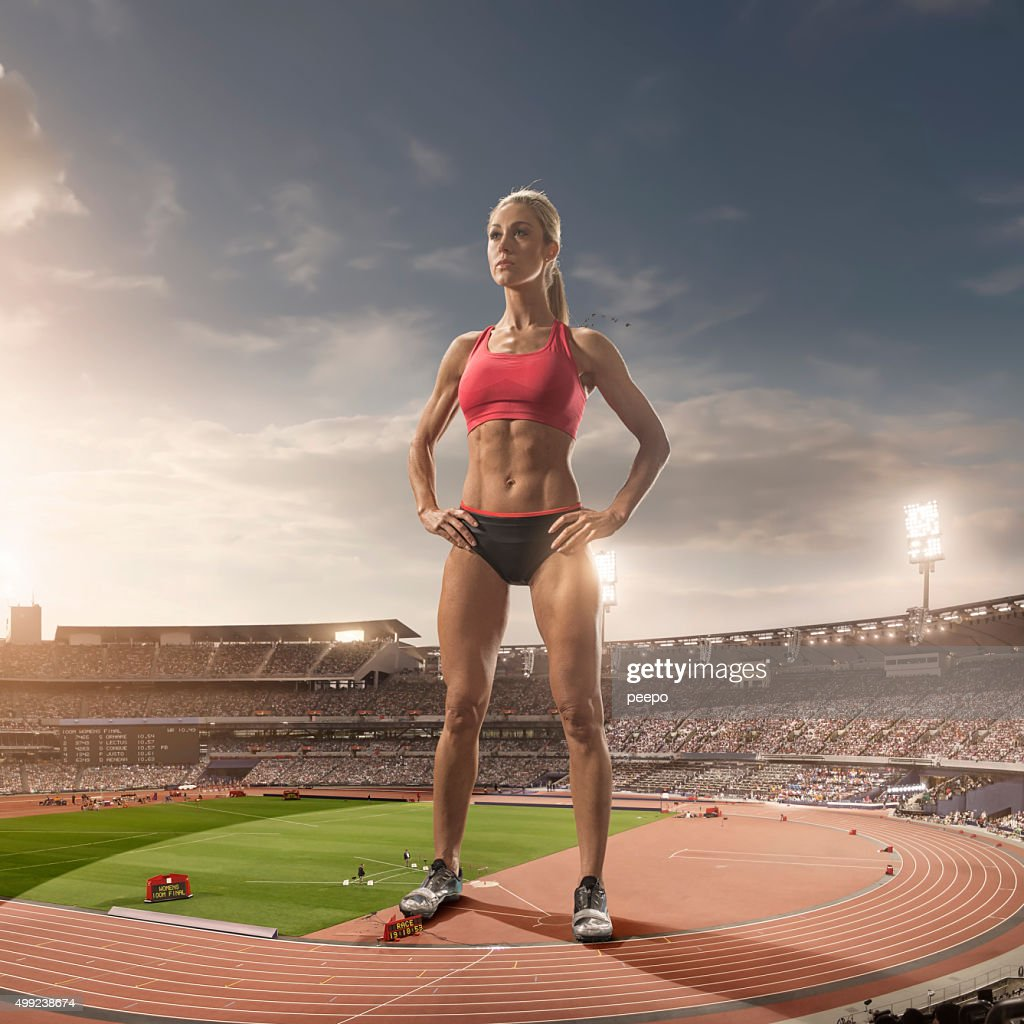 iant Woman Athlete Standing in Floodlit Athletics Stadium : Stock Photo
