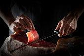 Iberian ham serrano ham slice cutting hands and knife