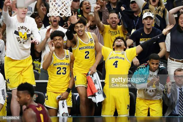 Ibi Watson, Jordan Poole and Isaiah Livers of the Michigan Wolverines react from the bench in the second half against the Loyola Ramblers during the...